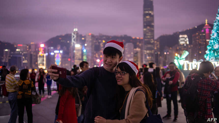 A couple clad in Santa hats pose for a selfie as the city skyline is seen along Hong Kong's Victoria Harbor, Dec. 25, 2018.