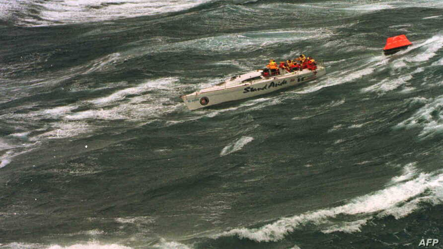 """The injured crew of demasted Australian yacht """"Stand Aside"""" await rescue by helicopter as they tow a life-raft in Bass Strait during the Sydney-to-Hobart ocean race, Dec. 27, 1998."""