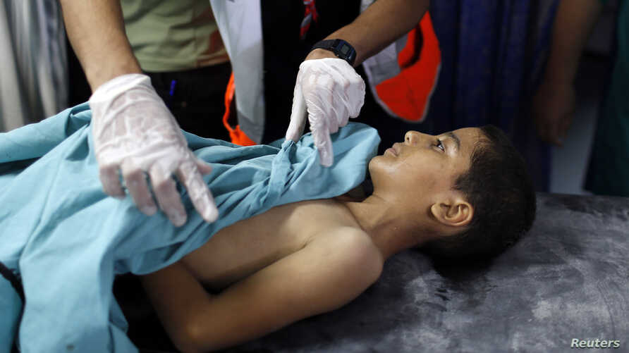 A boy is treated by medical staff after sustaining injuries from an explosion, at the Shifa hospital in Gaza City, August 8, 2014.