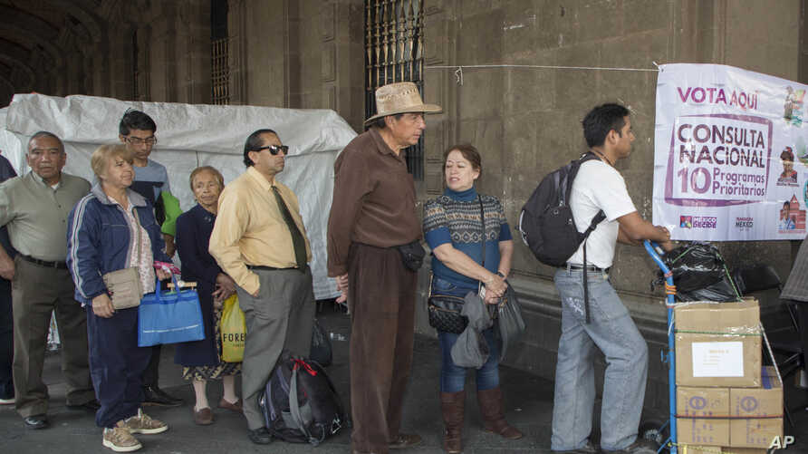 """Voters stand in line in Mexico City, Saturday, Nov. 24, 2018, to cast their decision on the referendum regarding the construction of the so called """"Mayan Train"""", that would connect several cities of the Yucatan peninsula."""