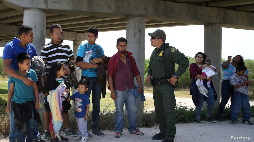 FILE - Border patrol agent Sergio Ramirez talks with immigrants who illegally crossed the border from Mexico into the U.S. in the Rio Grande Valley sector, near McAllen, Texas, April 2, 2018.