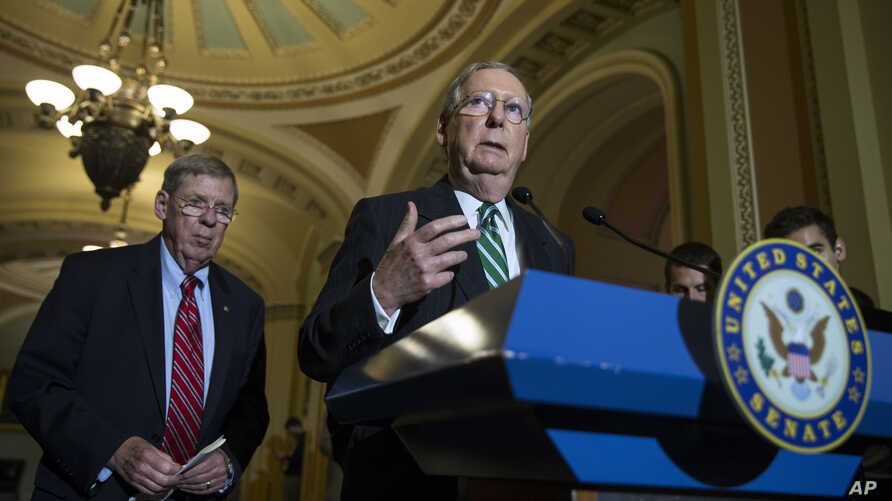 Senate Majority Leader Mitch McConnell of Ky., right, accompanied by Senate Veterans Affairs Committee Chairman Sen. Johnny Isakson, R-Ga., speaks during a news conference on Capitol Hill in Washington.
