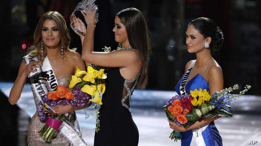 Former Miss Universe Paulina Vega, center, removes the crown from Miss Colombia Ariadna Gutierrez, left, before giving it to Miss Philippines Pia Alonzo Wurtzbach, right, at the Miss Universe pageant on Sunday, Dec. 20, 2015.