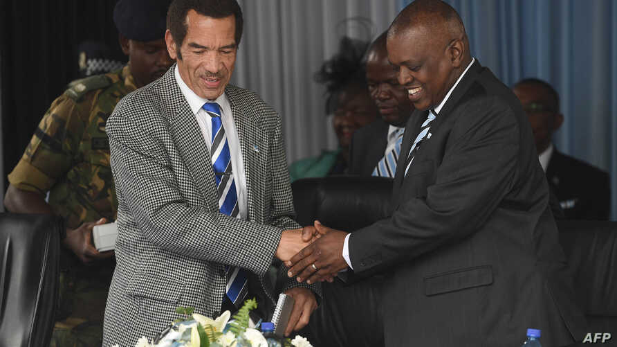 FILE - Botswana's President Seretse Ian Khama (L) shakes hands with his vice-president Mokgweetsi Masisi during a rally in his village Serowe on March 27, 2018, before officially stepping down on March 31 and handing power to his vice-president on Ap