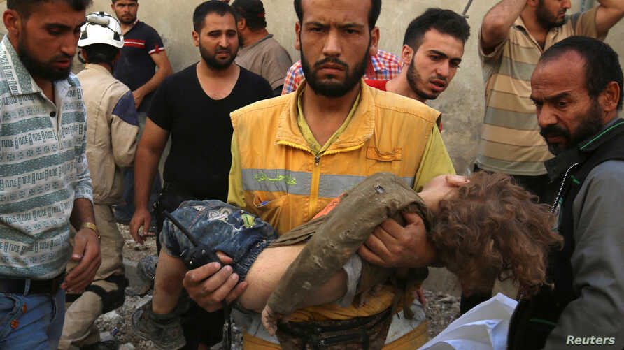 A medic carries the body of a child after airstrikes in the rebel-held Karam Houmid neighborhood in Aleppo, Syria, Oct. 4, 2016.