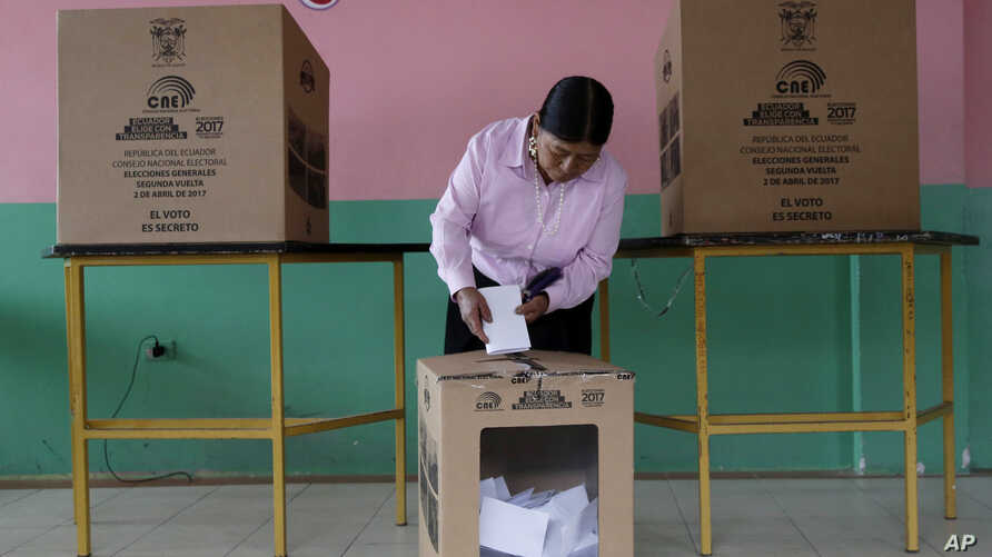 FILE - A woman casts her ballot during a presidential runoff election, in Quito, Ecuador, April 2, 2017.