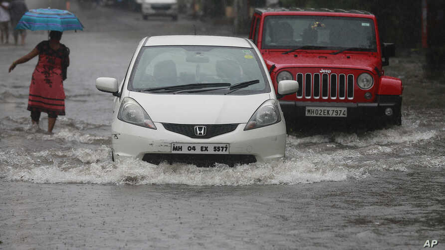Vehicles navigate their way through a flooded street in Mumbai, India, Sept. 20, 2017. Incessant rainfall in India's commercial capital has affected air and rail traffic.