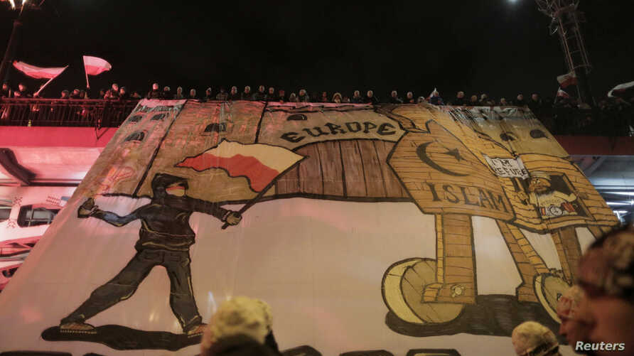 Protesters hold an anti-refugee banner during a rally, organized by far-right, nationalist groups, to mark the 99th anniversary of Polish independence in Warsaw, Nov. 11, 2017.