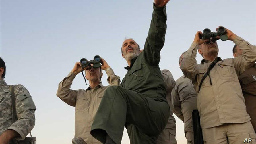 FILE - Photo by the government-controlled Syrian Central Military Media shows Iran's Army Chief of Staff Maj. Gen. Mohammad Bagheri, with binoculars, as he visits senior Iranian military officers in the northern province of Aleppo, Syria, Oct. 17, 20...