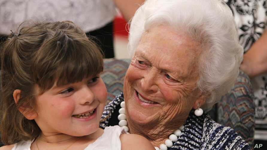 FILE - Mia Trumble, 7, sits on Barbara Bush's lap after the former first lady spoke at ceremony for Literacy Maine, June 15, 2011, in Biddeford, Maine.
