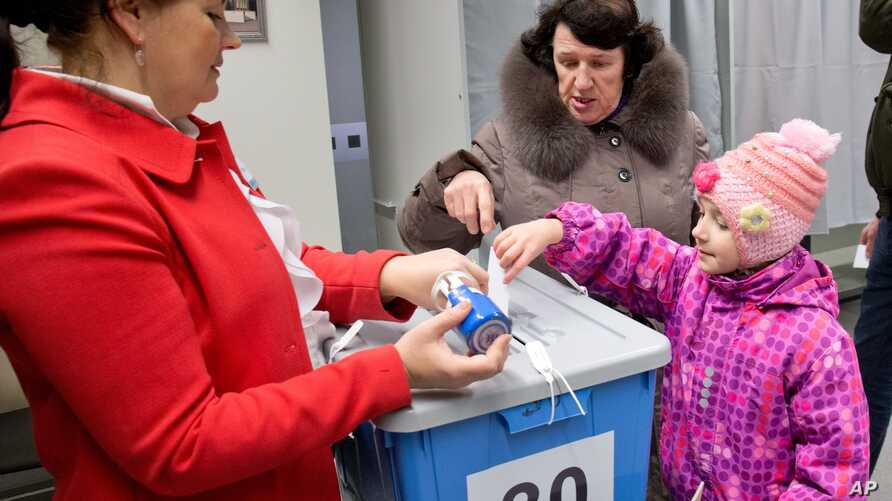 A little girl helps her mother to cast a ballot at a polling station in Tallinn, Estonia, Mar. 1, 2015.