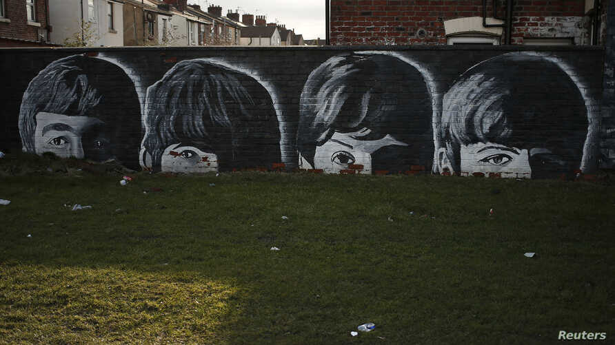 A mural of the Beatles is seen painted on the end of a row of terraced houses in Liverpool, northern England, Feb. 18, 2015.