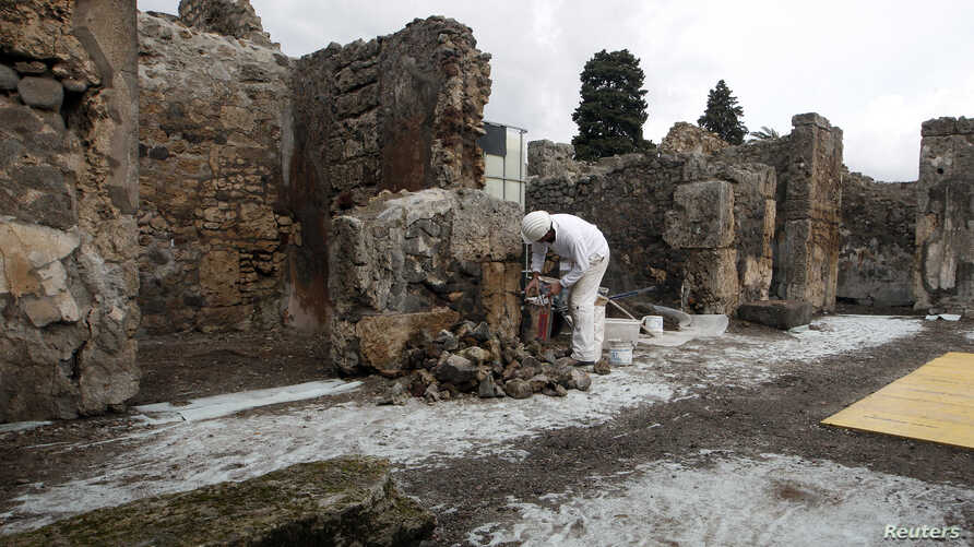 A restorer works in the ancient Roman city Pompeii, which was buried in AD 79 by an eruption of the Vesuvius volcano, Feb. 6, 2013.