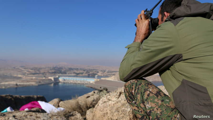 A fighter from the Syrian Democratic Forces takes a position atop Mount Annan overlooking the Tishrin Dam, after they captured it from Islamic State militants, south of Kobani, Syria, Dec. 27, 2015.
