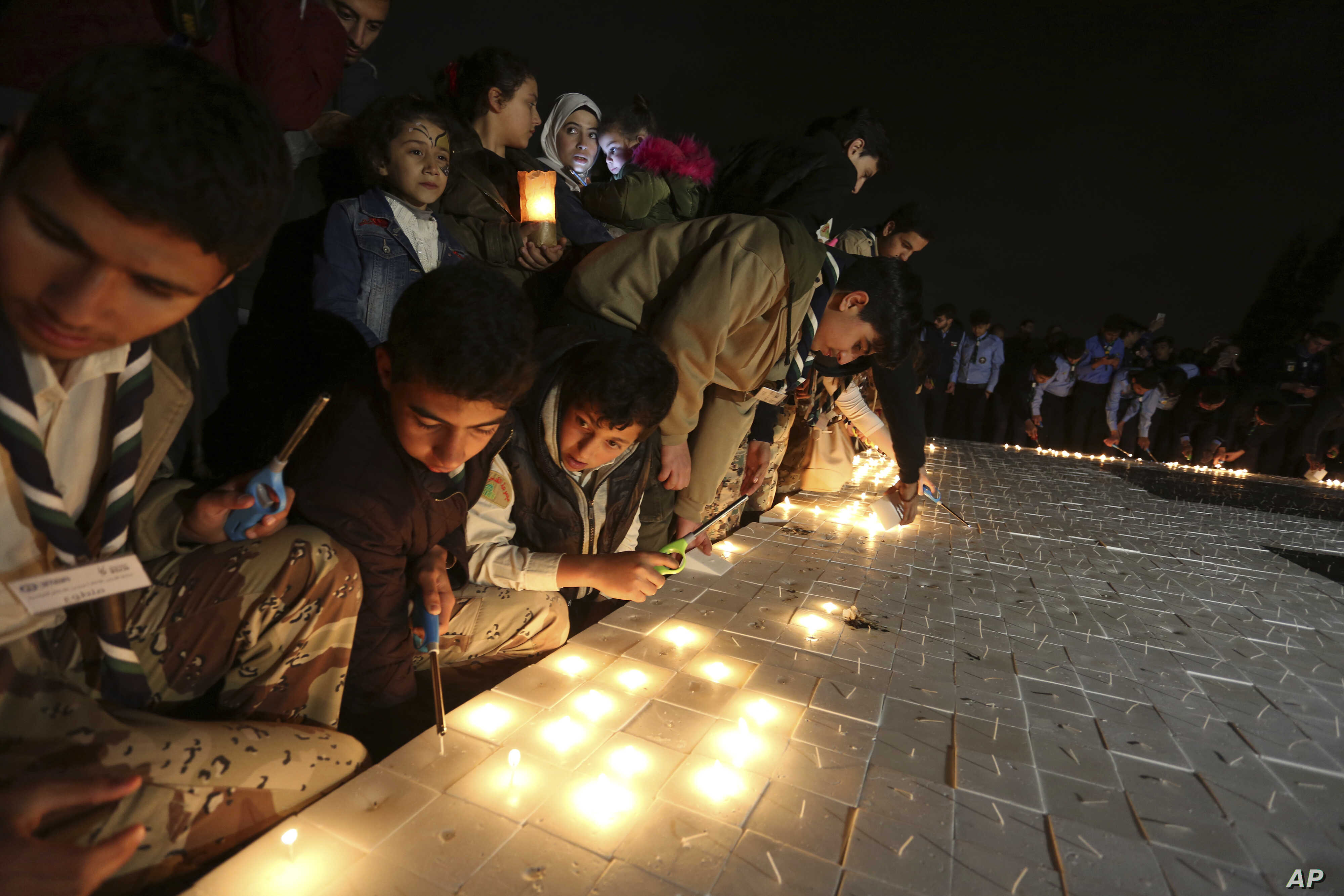 Jordanians light candles that form the Earth Hour logo, in an official attempt to be registered in the Guinness Book of Records for the largest candle-shaped World Hour logo, in Amman, Jordan, March 24, 2018.