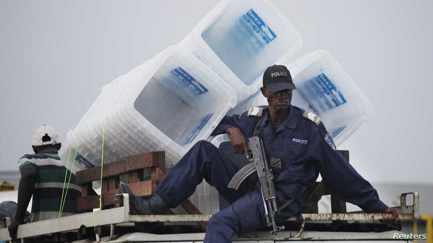 FILE - A policeman sits atop a minibus carrying empty ballot boxes to a central counting center in Democratic Republic of Congo's capital Kinshasa.