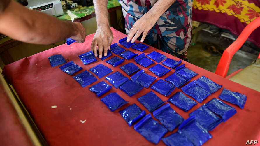 """A Bangladesh Border Guard (BGB) lays out small bags of the drug """"yaba"""" recovered from a passenger bus in a search at a checkpost along the Teknaf-Cox's Bazar highway in Teknaf, April 6, 2018."""