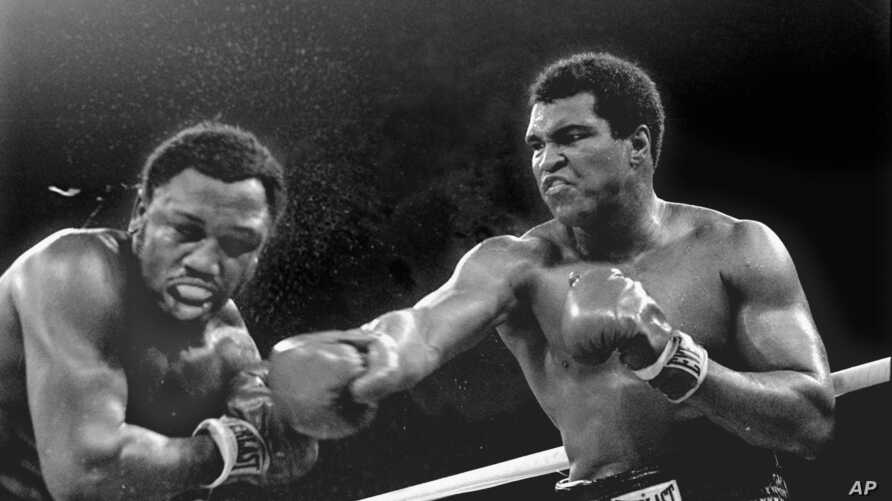 FILE - Spray flies from the head of challenger Joe Frazier as heavyweight champion Muhammad Ali connects with a right in the ninth round of their title fight in Manila, Philippines, Oct. 1, 1974. Ali has died, his family said, June 3, 2016. He was 74...
