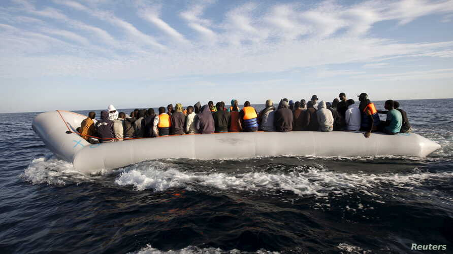 FILE - Migrants, who tried to flee to Europe, travel in a dinghy after they were stopped by Libyan coast guards and made to head to Tripoli, Sept.  29, 2015. The North African country has turned into a major hub for human traffickers smuggling Africa
