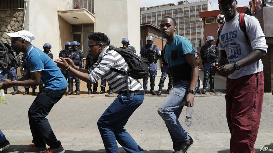 South Africa University Protests: Protesting students from the University of the Witswatersrand sing outside the Hillbrow Magistrate's Court in Johannesburg, South Africa, Wednesday, Oct. 12, 2016, in support of their peers who were arrested earlier