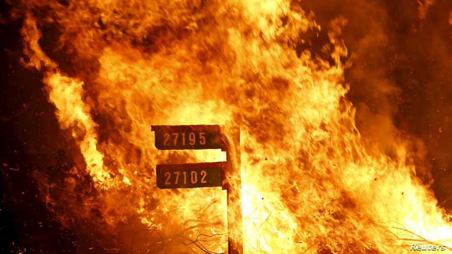 Flames from the Jerusalem Fire consume a sign containing addresses to homes along Morgan Valley Road in Lake County, California, August 12, 2015.