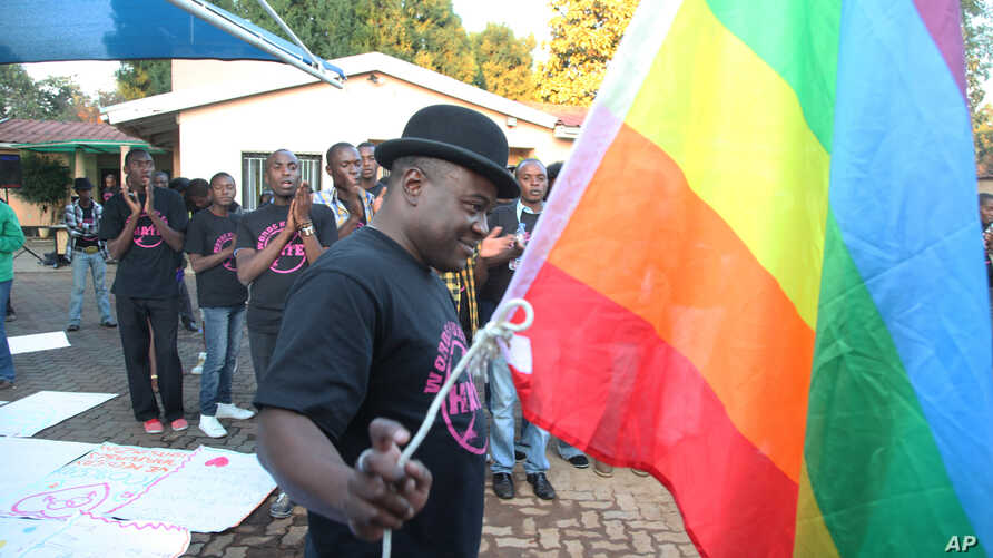 Samba Chesterfield, Director of Gays and Lesbians Association of Zimbabwe, prepares to hoist their official flag alongside the  Zimbabwean flag during an event in Harare, Zimbabwe, May, 19, 2012.