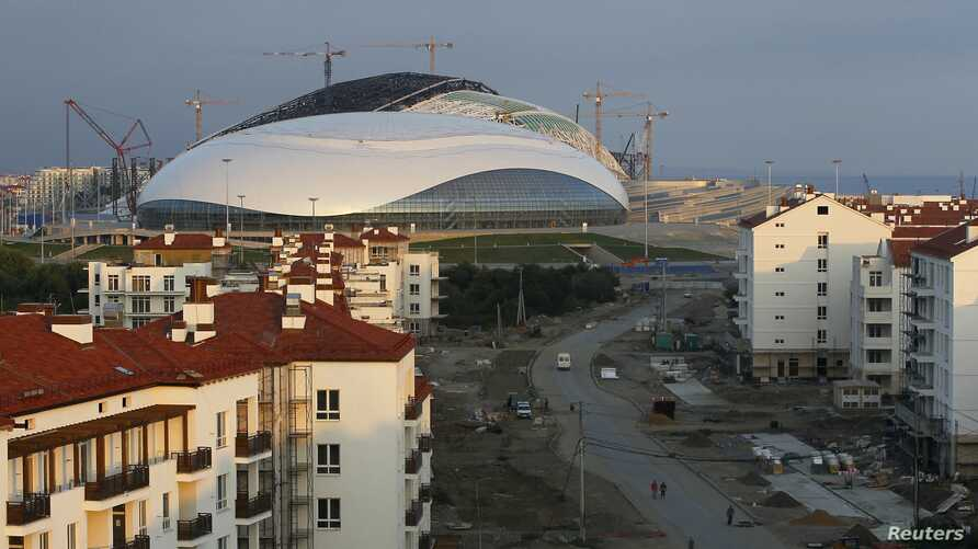 Workmen walk through the under construction Olympic Village, which sits in front of the Bolshoy Ice Dome on the Olympic Park for the Sochi 2014 Winter Olympic Games, in Adler, Russia, Aug. 19, 2013.