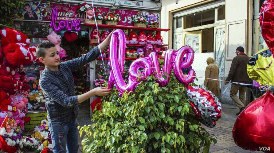 """A balloon spelling out """"LOVE"""" is added to a plant at an Egyptian flower shop. (H. Elrasam/VOA)"""