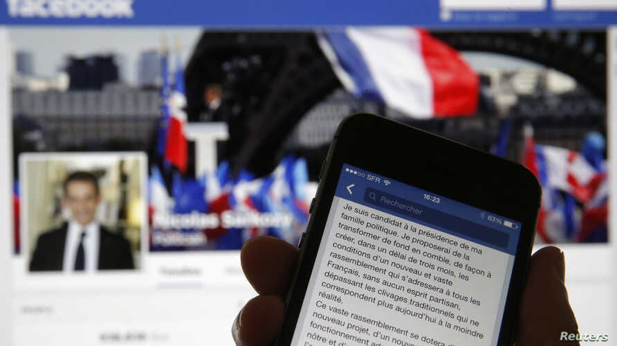 An illustration photo shows the message of former French President Nicolas Sarkozy on his Facebook page displayed on a mobile phone internet browser held in front of a computer screen which also displays his Facebook page in Paris, Sept. 19, 2014.