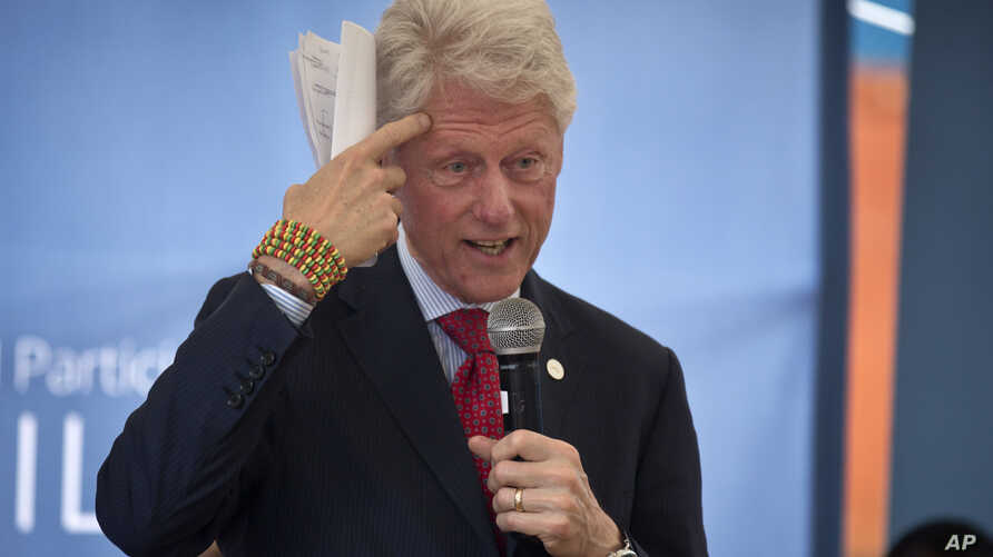 """Former president Bill Clinton gestures while wearing a bracelet given to him by Kenyan students, as he and and his daughter Chelsea Clinton talk about their foundation's """"No Ceilings"""" at Farasi Lane Primary School in Nairobi, Kenya, May 1, 2015."""