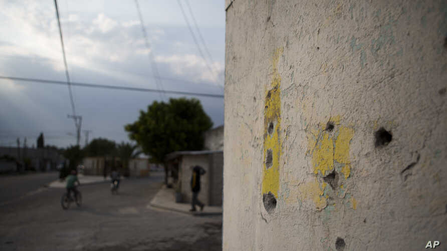 Bullet holes mark a wall at an intersection where a video released by Mexican media outlets appeared to show a soldier executing a civilian lying face down in the street with a shot to the back of his head, in Palmarito Tochapan, Puebla State, May 10
