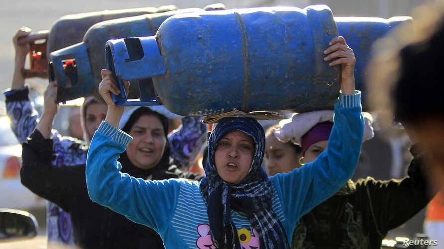 Women carry gas cylinders to fill them at a distribution point in Cairo January 19, 2015. Egypt is going through its worst energy crisis in decades and is seeking fresh sources of natural gas, which powers most of its homes and factories. REUTERS/Moh