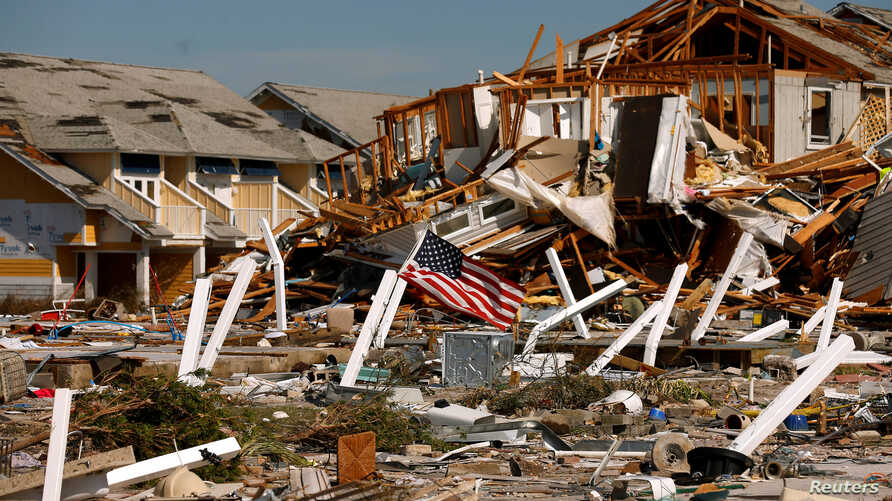 An American flag flies amongst rubble left in the aftermath of Hurricane Michael in Mexico Beach, Florida, Oct. 11, 2018.