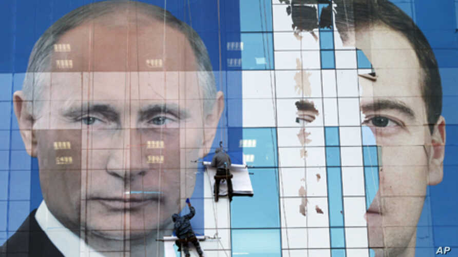 Workers attach a pre-election poster featuring Russia's President Dmitry Medvedev (r) and Prime Minister Vladimir Putin in Krasnodar, November 24, 2011