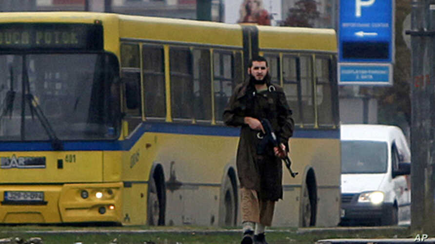 A gunman with an automatic weapon walks in Sarajevo, after he fired shots at the US embassy, October 28, 2011.