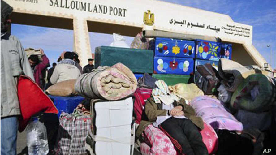 An Egyptian, who has just crossed Salloum land port gate with Libya, at background, takes a nap over his luggage. Thousands of other foreigners were still stranded, February 23, 2011