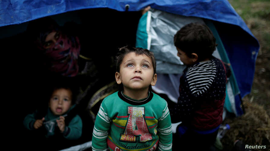 FILE PHOTO: A Syrian refugee boy stands in front of his family tent at a makeshift camp for refugees and migrants next to the Moria camp on the island of Lesbos, Greece, Nov. 30, 2017.
