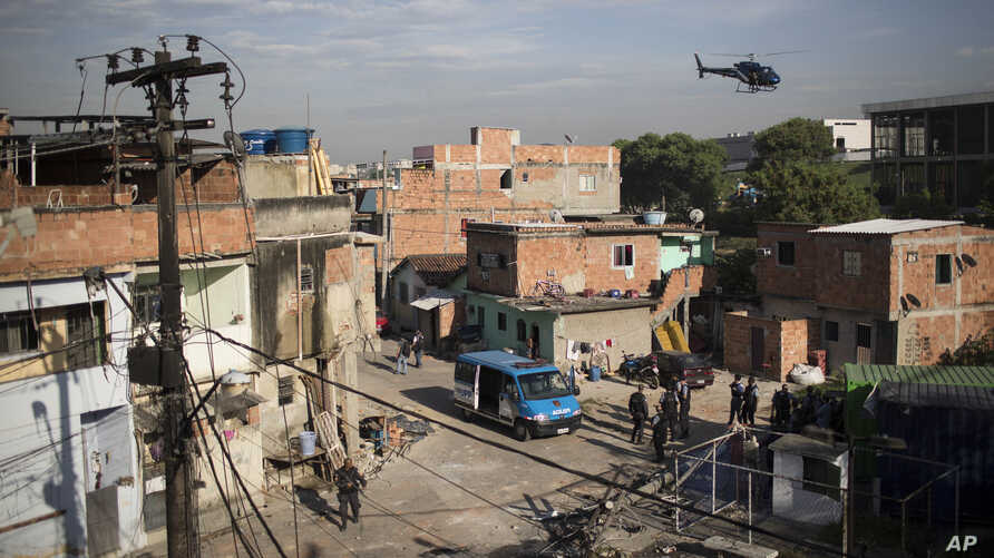 A military police helicopter flies over the Mandela shantytown, part of the Manguinhos slum complex, as policemen patrol the area on the ground after attacks to their Pacifying Police Unit post in Rio de Janeiro, Brazil, March 21, 2014.