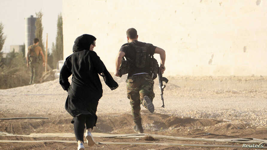 A woman reporter runs with a rebel fighter to avoid snipers at the frontline against the Islamic State fighters in Aleppo's northern countryside, Syria, Oct. 10, 2014.