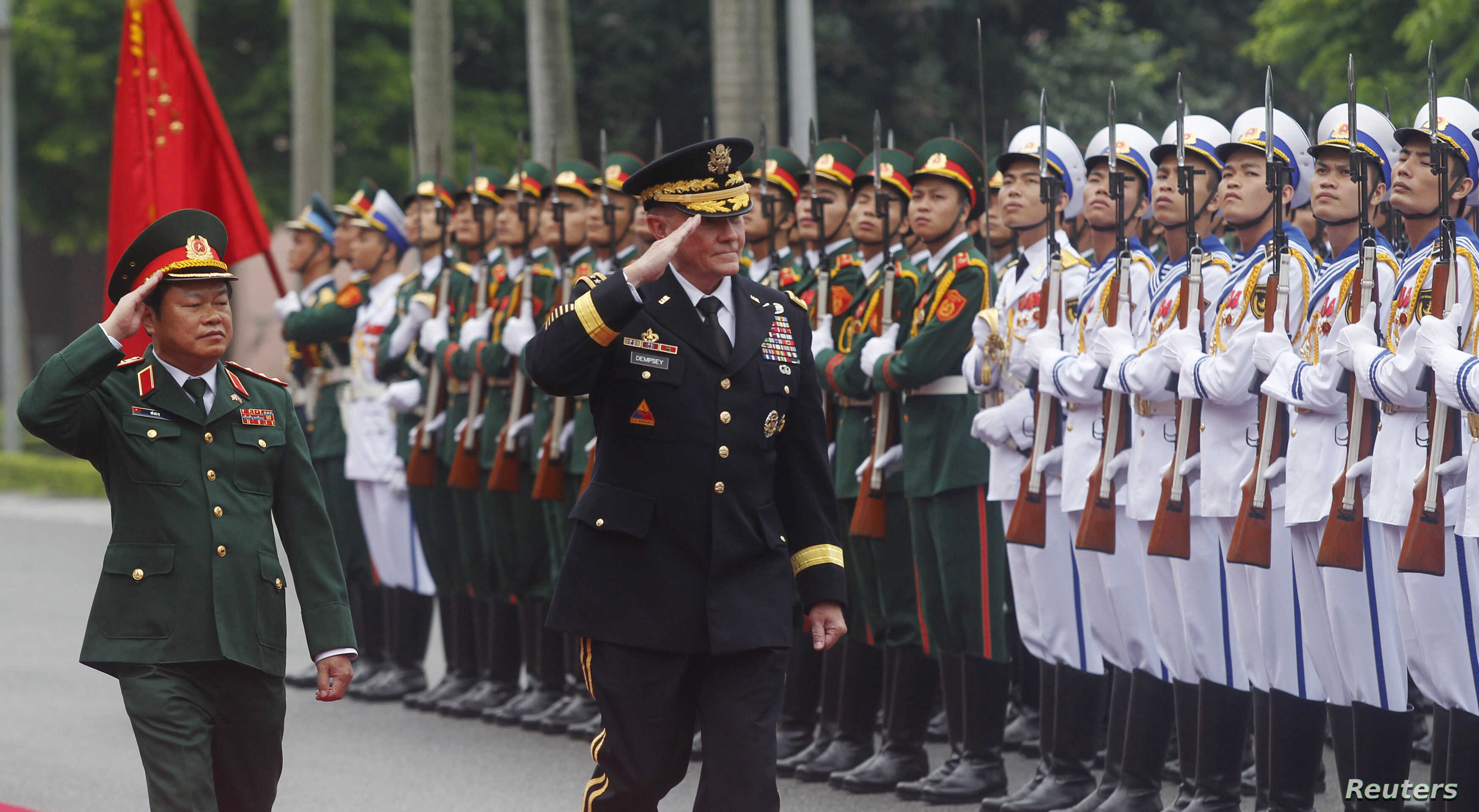 U.S. Chairman of the Joint Chiefs of Staff General Martin Dempsey (C) reviews the guard of honour with his Vietnamese counterpart General Do Ba Ty during a welcoming ceremony at Vietnam's Defence Ministry in Hanoi August 14, 2014.