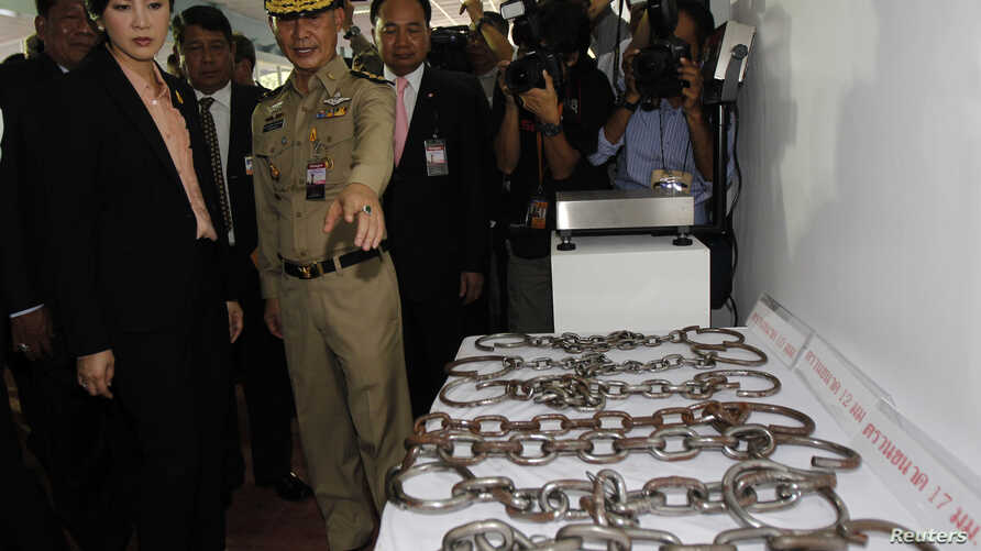 FILE - Thailand's Prime Minister Yingluck Shinawatra looks at chains on display at Bang Kwang Central Prison, May 15, 2013. Thailand announced that they will stop using manacles on inmates.