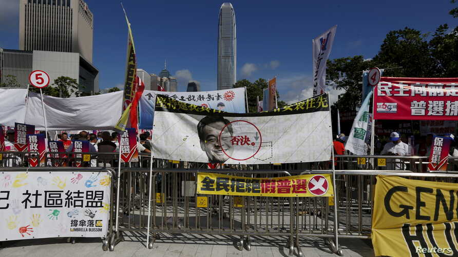 A banner featuring a portrait of Hong Kong Chief Executive Leung Chun-ying with a veto sign set up by pro-democracy protesters, is displayed in front of a pro-China rally outside Legislative Council in Hong Kong, China, June 18, 2015.