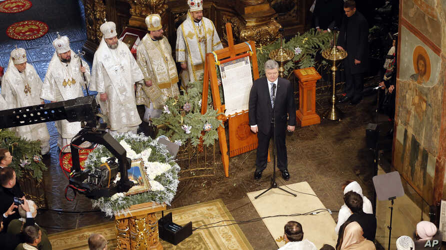 "Ukrainian President Petro Poroshenko delivers a speech standing next to the ""Tomos"" decree of autocephaly for the Orthodox Church of Ukraine during the service marking Orthodox Christmas and celebrating the independence of the Ukrainian Orthodox Chur"