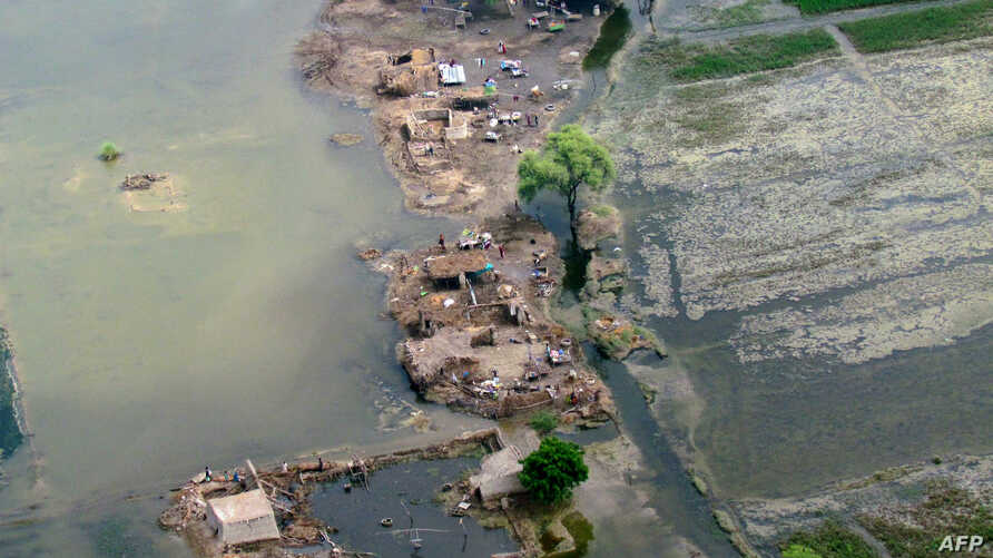 Pakistani flood affected villagers seek refuge on a dry patch in the flood-hit Jacobabad district of Sindh province, September 17, 2012.
