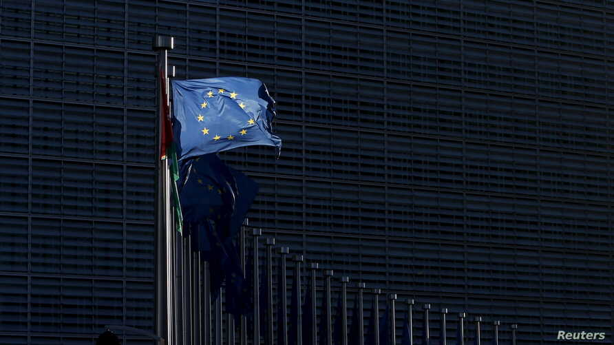 FILE - A ripped European Union flag flutters outside EU Commission headquarters in Brussels, Belgium, Jan. 12, 2016.