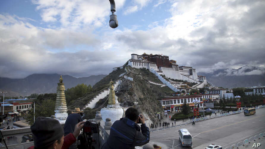 In this Sept. 19, 2015 file photo, tourists take photos of the Potala Palace beneath a security camera in Lhasa, capital of the Tibet Autonomous Region of China.