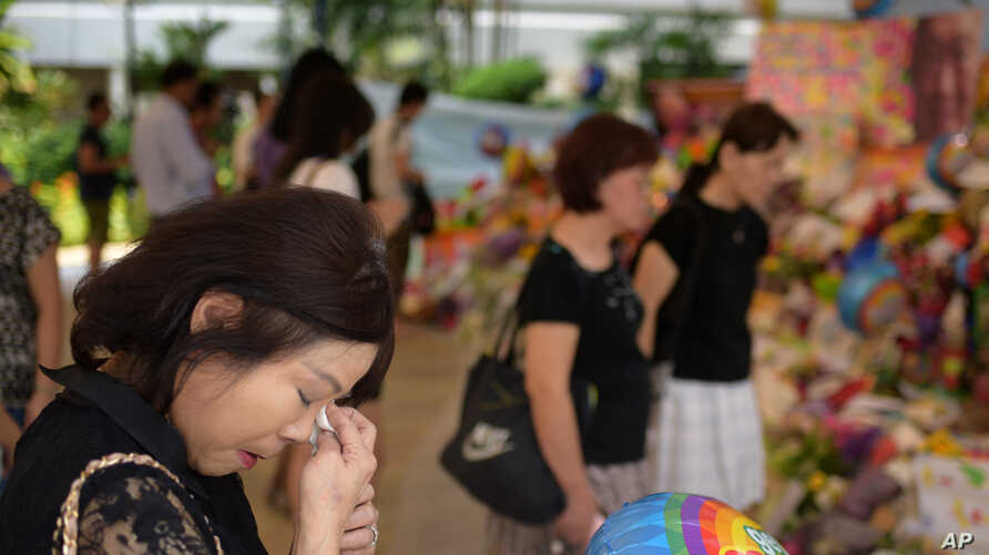 Sarah Kee, 61, of Singapore, wipes her tears at an area set aside for tributes to former Singapore Prime Minister Lee Kuan Yew at the hospital where he passed away, Monday, March 23, 2015 in Singapore. Kee remembers waving to Lee's motorcade daily as