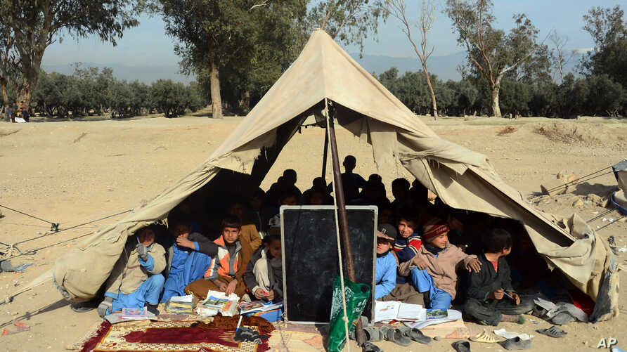 Afghan students attend a school class under a tent in Jalalabad, capital of Nangarhar province, Afghanistan, Dec. 16, 2015.
