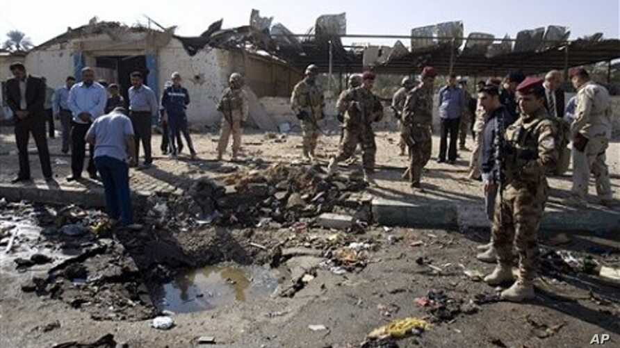 Iraqi security forces inspect the scene of a car bomb attack in Karbala, 50 miles (80 kilometers) south of Baghdad, 8 Nov. 2010.