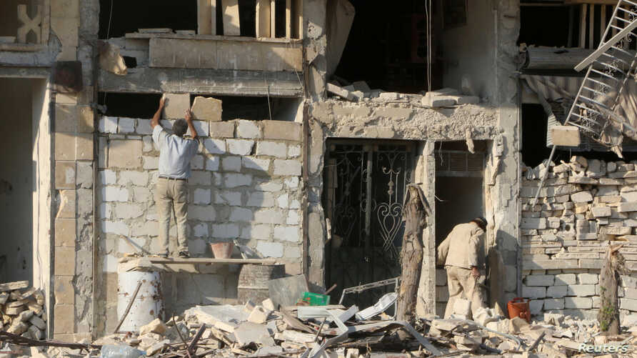 A man rebuilds a wall of a damaged building in the rebel held al-Katerji district in Aleppo, Syria, Aug. 13, 2016.